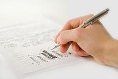 Mano masculina con las cartas de asunto y el gráfico de barra imagenes de archivo