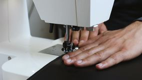 Mano masculina de la costurera que sostiene el cuero detrás de la máquina de coser almacen de video