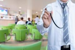 Mano masculina del doctor de la medicina que sostiene el estetoscopio con waiti paciente foto de archivo libre de regalías
