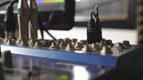 Mano masculina del ingeniero de sonido que tapa el cable de audio de un panel del mezclador Redactor audio que trabaja en el estu metrajes