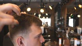 Mano masculina del peluquero que peina el pelo del hombre joven en barbería Individuo hermoso que consigue su pelo vestido en el  metrajes