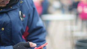 Mano masculina en guantes sin dedos viejos usando el teléfono del tacto, mensaje que manda un SMS del pobre hombre metrajes