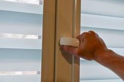 Mano masculina en la manija plástica blanca del vidrio de la ventana fotografía de archivo