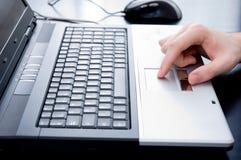 Mano masculina en touchpad del cuaderno Imagen de archivo