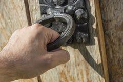Mano masculina que abre la puerta de madera vieja con el tirador de puerta muy viejo Fotografía de archivo libre de regalías