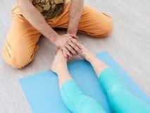 Mano masculina que aplica la presión en las piernas de las mujeres Foto de archivo libre de regalías