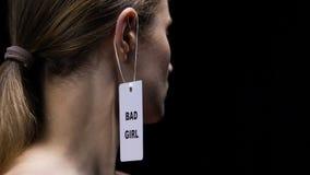 Mano masculina que cuelga la mala etiqueta de la muchacha en el oído femenino, la falta de respeto social y la presentación almacen de metraje de vídeo