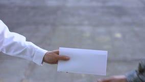 Mano masculina que da el sobre blanco al soldado, pago del sueldo, acuerdo del soborno metrajes