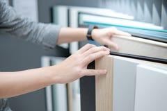 Mano masculina que elige los materiales del gabinete o de la encimera imagenes de archivo