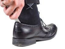 Mano masculina que entra en el calcetín negro a pie en el zapato de cuero con el calzador Imagen de archivo libre de regalías