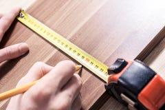 Mano masculina que hace a Mark At The Measuring Point de una cinta métrica en un tablero de madera de Brown imagen de archivo libre de regalías