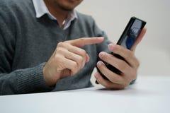 Mano masculina que juega el negro del smartphone fotos de archivo libres de regalías