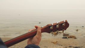 Mano masculina que juega sobre los acordes en la guitarra contra la perspectiva del mar jugar la opinión trasera de la guitarra metrajes