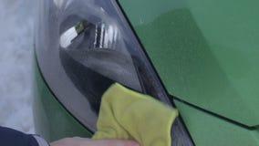 Mano masculina que limpia las linternas sucias del coche al aire libre metrajes