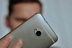 Mano masculina que lleva a cabo un teléfono móvil elegante de plata mientras que toma el selfie Imagenes de archivo