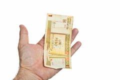 Mano masculina que lleva a cabo una cuenta de los Pesos cubanos aislada en el fondo blanco Imagenes de archivo