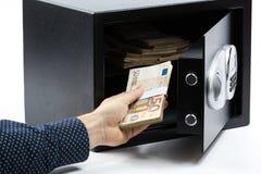 Mano masculina que mantiene billetes de banco euro una caja de depósito seguro Imagenes de archivo