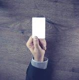 Mano masculina que pasa la tarjeta de visita en blanco con el espacio de la copia Imágenes de archivo libres de regalías
