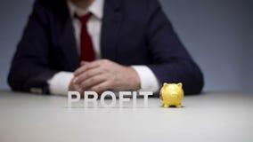 Mano masculina que pone la moneda en caja de dinero de los cerdos Beneficio de la acumulación en negocio moderno metrajes