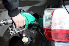 Mano masculina que rellena el coche negro con el combustible en una estación de servicio Foto de archivo libre de regalías
