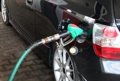 Mano masculina que rellena el coche negro con el combustible en una estación de servicio imagenes de archivo