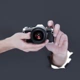 Mano masculina que se rompe a través del fondo de papel negro y que sostiene la cámara retra Imagen de archivo libre de regalías