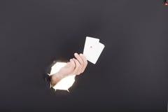 Mano masculina que se rompe a través del fondo de papel y que sostiene la tarjeta de visita De alta resolución Foto de archivo libre de regalías