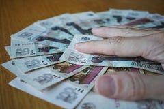 Mano masculina que se sostiene los fingeres en el círculo creado de las rublos rusas de la moneda rusa en la tabla de madera Imagenes de archivo