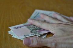 Mano masculina que se sostiene los fingeres en las rublos rusas de la moneda rusa en la tabla de madera Fotos de archivo