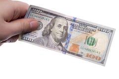 Mano masculina que sostiene cientos billetes de banco del dólar en el backgroun blanco Imágenes de archivo libres de regalías