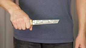 Mano masculina que sostiene el cuchillo japonés con la funda para el cierre que lucha para arriba almacen de video