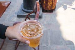 Mano masculina que sostiene el vidrio de cerveza en el frente del restaurante Imagen de archivo