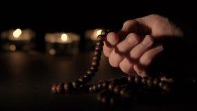 Mano masculina que sostiene gotas del rosario metrajes