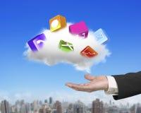 Mano masculina que sostiene la nube blanca con los bloques coloridos del app Imagen de archivo