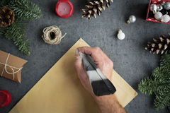 Mano masculina que sostiene la pluma disponible de la tinta y que escribe la letra a Papá Noel Fotografía de archivo