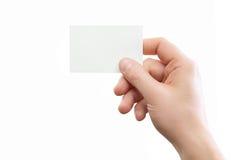 Mano masculina que sostiene la tarjeta de visita blanca en el fondo Fotografía de archivo
