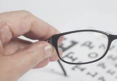 Mano masculina que sostiene las lentes negras para la carta de prueba del examen de la vista de la visión fotos de archivo