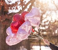 Mano masculina que sostiene los globos del corazón Fotografía de archivo libre de regalías