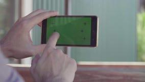 Mano masculina que sostiene smartphone con la pantalla verde almacen de metraje de vídeo