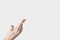 Mano masculina que sostiene un cigarrillo aislado en gris imagenes de archivo