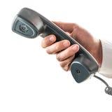 Mano masculina que sostiene un receptor de teléfono fotografía de archivo libre de regalías