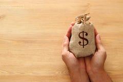 Mano masculina que sostiene un saco de dinero sobre el escritorio de madera imágenes de archivo libres de regalías