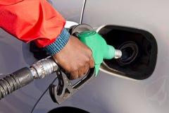 Mano masculina que sostiene un surtidor de gasolina verde Foto de archivo