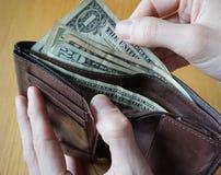 Mano masculina que sostiene una cartera de cuero y que retira la moneda americana (USD, dólares de EE. UU.) Foto de archivo libre de regalías