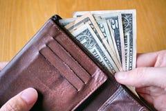 Mano masculina que sostiene una cartera de cuero y que retira la moneda americana (USD, dólares de EE. UU.) Fotos de archivo