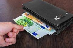 Mano masculina que sostiene una cartera de cuero y que retira el euro europeo EUR de la moneda imagen de archivo libre de regalías