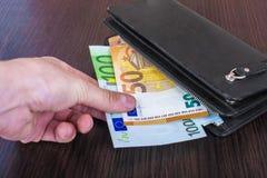 Mano masculina que sostiene una cartera de cuero y que retira el euro europeo EUR de la moneda foto de archivo