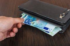 Mano masculina que sostiene una cartera de cuero y que retira el euro europeo EUR de la moneda imagenes de archivo