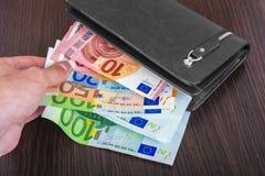 Mano masculina que sostiene una cartera de cuero y que retira el euro europeo EUR de la moneda imágenes de archivo libres de regalías