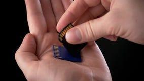 Mano masculina que sostiene una tarjeta del SD de la tarjeta de memoria - tarjeta de Secure Digital usada en las cámaras de vídeo almacen de video